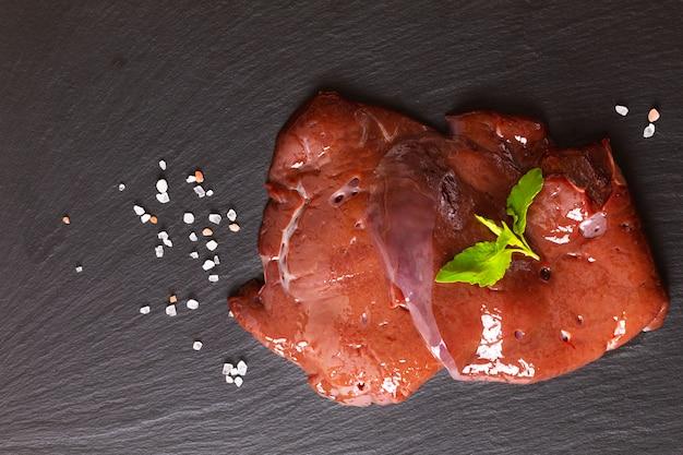 Conceito de alimentos orgânicos frescos fatia fígado de carne crua na placa de ardósia preta