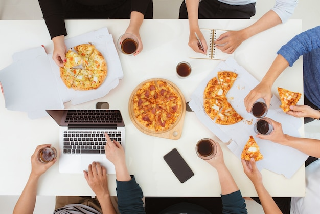 Conceito de almoço e pessoas. equipe de negócios feliz comendo pizza no escritório