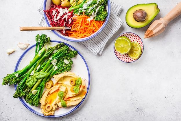 Conceito de almoço vegan. salada vegetal e broccolini do arco-íris com hummus.