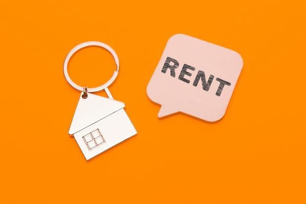 Conceito de aluguel. chaveiro de metal em forma de uma casa e um adesivo com a inscrição - alugue em um fundo laranja.