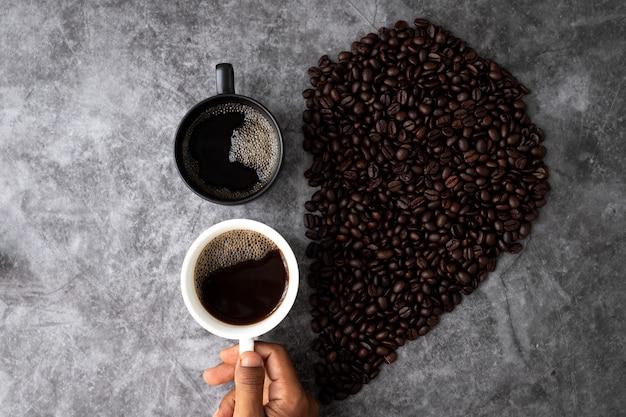 Conceito de amante do café preto, mão segure uma xícara de café, vista de cima da mesa.
