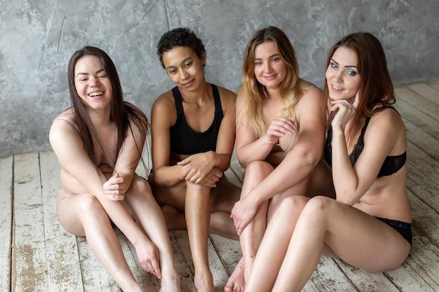 Conceito de amizade, beleza, corpo positivo e pessoas - grupo de mulheres felizes diferentes em roupas íntimas sobre fundo cinza. foto de alta qualidade