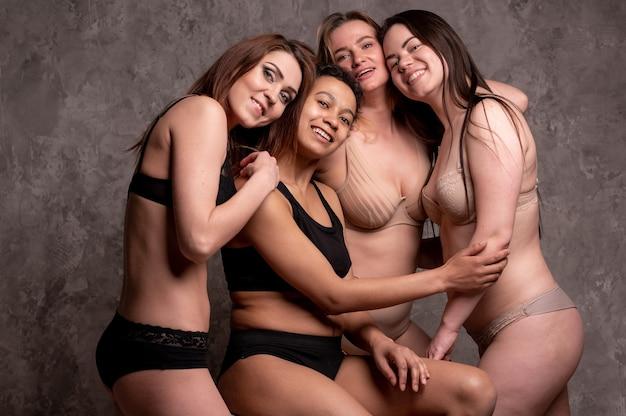 Conceito de amizade, beleza, corpo positivo e pessoas - grupo de mulheres felizes diferentes em roupas íntimas sobre fundo cinza