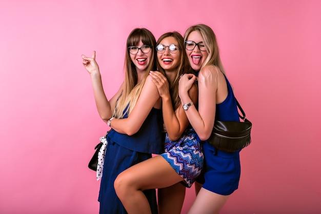 Conceito de amizade de relaã§ã £ o positiva, trãªs mulheres bonitas e alegres se divertindo juntas, abraã§os e emoã§ãµes surpresas, roupas e acessã³rios de noite combinando, emoticons fofos, tempo de festa em grupo.