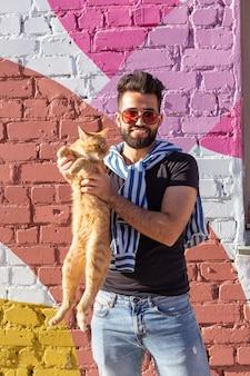 Conceito de amizade e animais de estimação - jovem bonito com um gato fofo ao ar livre