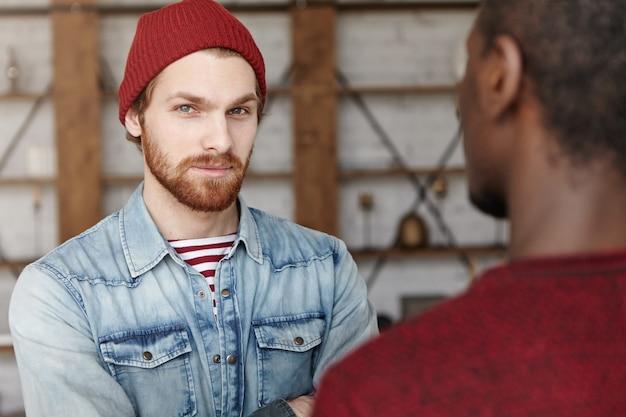 Conceito de amizade e parceria inter-racial. dois melhores amigos, reunião no café, discutindo planos e idéias de seu projeto de negócio comum promissor, homem barbudo branco de chapéu olhando