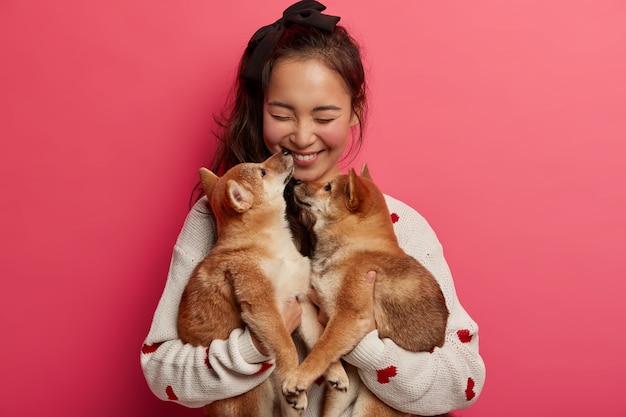 Conceito de amizade humana e animal. menina alegre feliz por ganhar dois filhotes com pedigree em seu aniversário, beija o animal de estimação