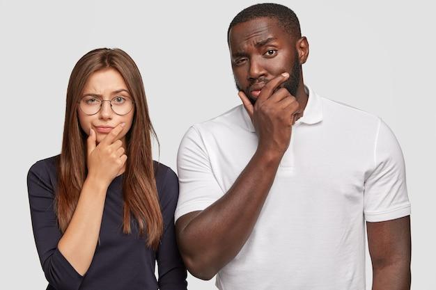 Conceito de amizade multiétnica. mulher caucasiana duvidosa e pensativa e um homem negro bonito seguram o queixo e têm expressões confusas