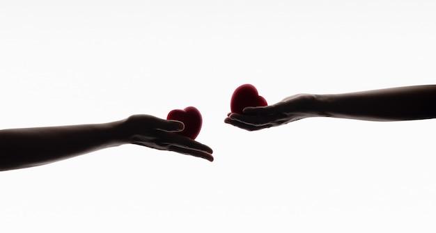Conceito de amor, cuidado, doação e compartilhamento. silhueta de mãos com símbolo de coração