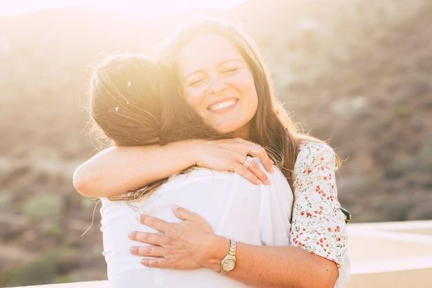 Conceito de amor e amizade com duas mulheres jovens amigas se abraçando e sorrindo com amor - diversidade para pessoas brancas - amor alternativo - sol na luz de fundo com efeito de luz