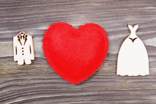 Conceito de amor e casamento. coração vermelho e vestidos de noiva em miniatura em madeira.