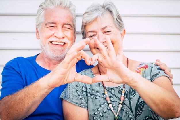 Conceito de amor e dia dos namorados para um casal feliz e alegre, um homem sênior e uma mulher caucasiana, juntos fazendo uma lareira com as mãos e sorrindo - felicidade após a vida juntos para sempre