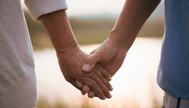 Conceito de amor e dia dos namorados. um casal feliz de idosos segurando a mão durante o pôr do sol