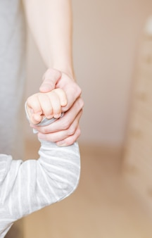 Conceito de amor e família. mãos da mãe e do bebê, closeup.