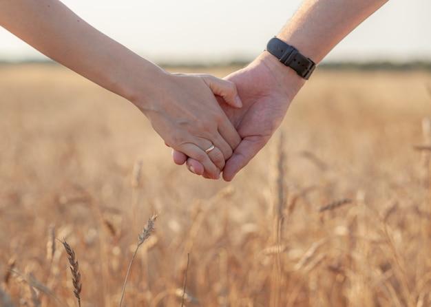Conceito de amor. um casal de mãos dadas durante o pôr do sol, um símbolo de amor e relacionamento feliz. um jovem casal apaixonado caminha por um campo de trigo ao pôr do sol, de mãos dadas e olhando o pôr do sol