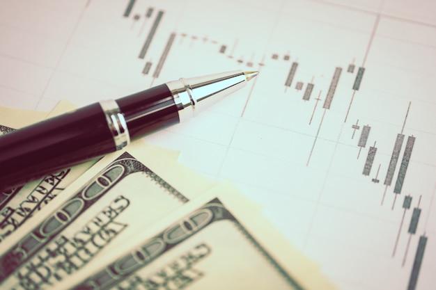 Conceito de análise de mercado de moeda. caneta em um gráfico conosco dólares. em tons.