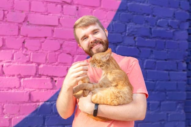 Conceito de animais de estimação e animais - jovem bonito com um lindo gato vermelho ao ar livre.