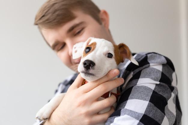 Conceito de animais e animais de estimação de pessoas perto de jovem segurando o cachorrinho jack russell terrier
