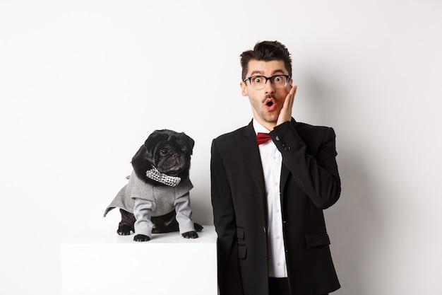 Conceito de animais, festa e celebração. homem bonito chocado em um terno formal e cachorro bonito fantasiado, olhando para a câmera espantado, em pé sobre o branco