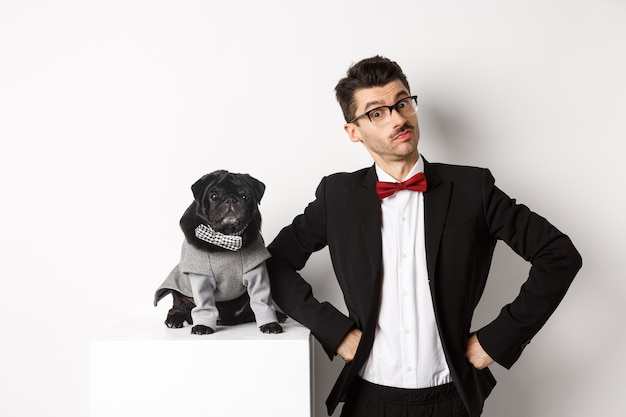 Conceito de animais, festa e celebração. jovem bonito e cachorrinho em trajes formais, olhando para a câmera, em pé sobre o branco.