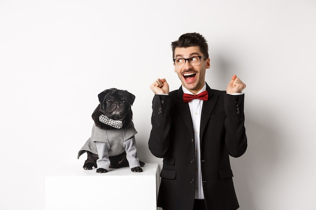 Conceito de animais, festa e celebração. proprietário de cachorro alegre em terno em pé perto de pug preto bonito fantasiado, regozijando-se e comemorando a vitória, em pé sobre branco.