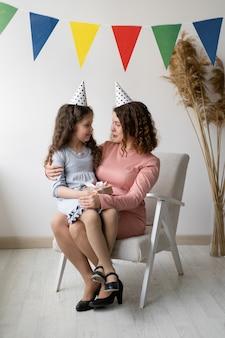 Conceito de aniversário. a menina senta nos braços de sua mãe
