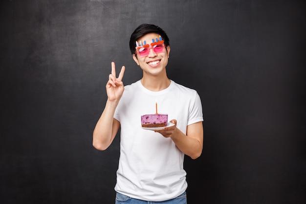 Conceito de aniversário, comemoração e festa. amigável homem feliz comemorando b-dia segurando o bolo no prato com vela acesa, soprando para fazer um desejo, mostrar sinal de paz, suporte