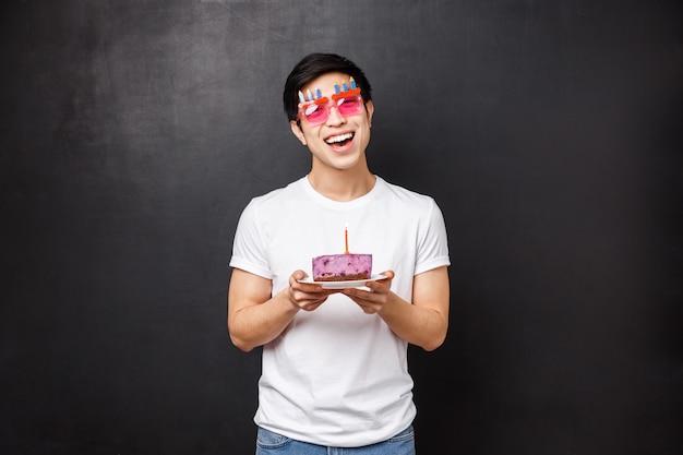 Conceito de aniversário, comemoração e festa. entusiasmado bonitão asiático comemorando o dia b, incline a cabeça e olhe a câmera feliz com sorriso satisfeito, segure o bolo no prato com vela acesa, fazendo desejo
