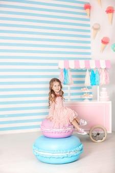 Conceito de aniversário e felicidade - feliz menina sentada em um bolo grande