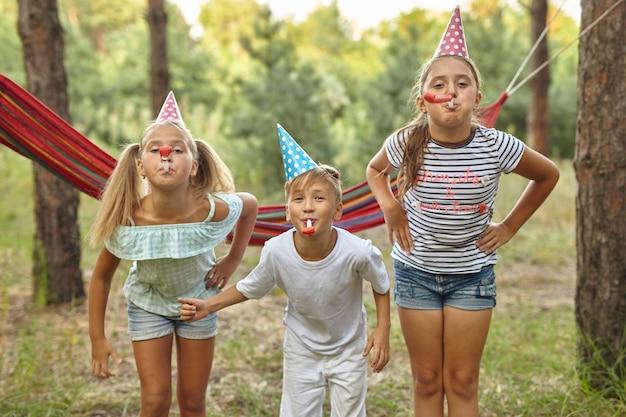 Conceito de aniversário, infância e celebração - perto de crianças felizes tocando buzinas e se divertindo no verão ao ar livre