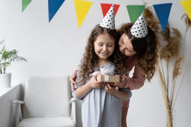 Conceito de aniversário. jovem mãe e sua linda filha estão sorrindo