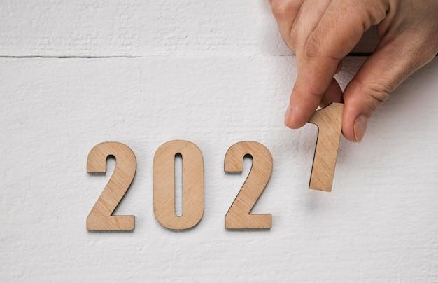 Conceito de ano novo 2021. mão feminina colocando números de madeira 2021 na mesa de madeira