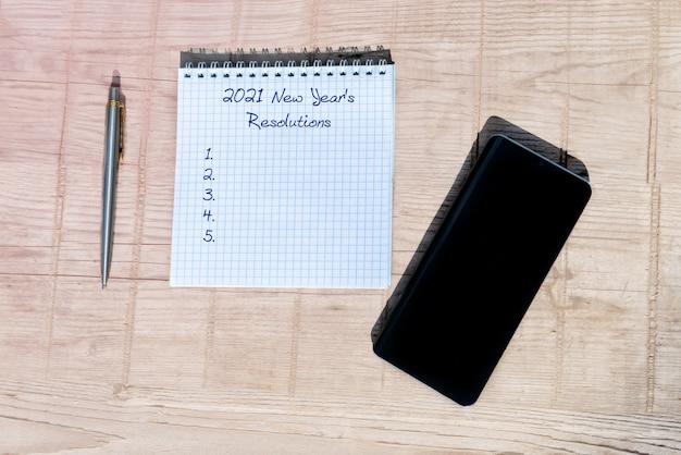 Conceito de ano novo - 2021 número e texto no bloco de notas. smartphone, bloco de notas e caneta sobre uma mesa de madeira.