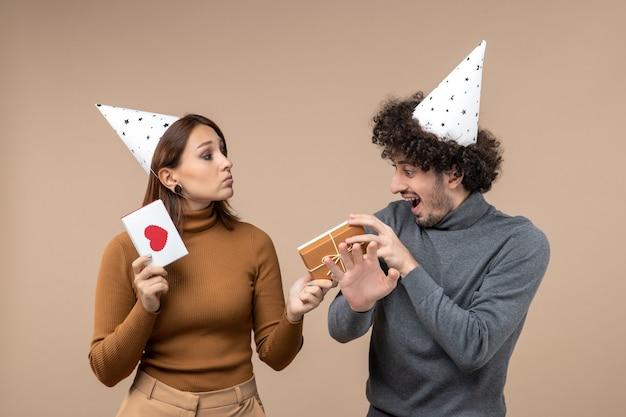 Conceito de ano novo com jovem casal usando menina de chapéu de ano novo com coração e presente e cara na filmagem cinza