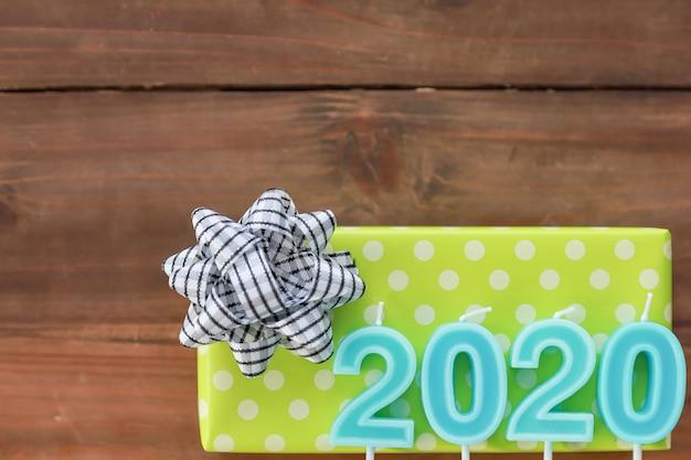 Conceito de ano novo de 2020. vista superior da luz do número - vela azul em caixas de presente verdes e brancas do ponto na prancha de madeira velha e rachada com espaço da cópia para o texto.