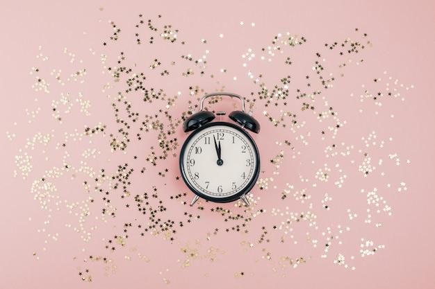 Conceito de ano novo. despertador com confete dourado