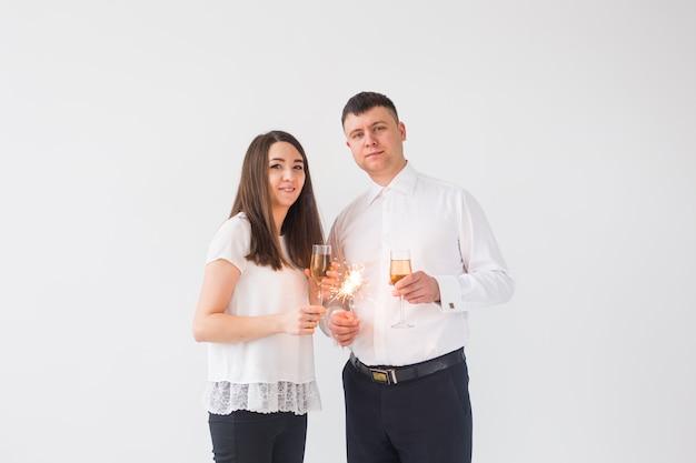Conceito de ano novo, feriados, data e dia dos namorados - casal apaixonado segurando a luz de estrelinhas