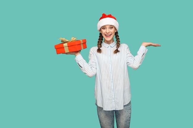 Conceito de ano novo. garota bonita feliz em camisa azul clara listrada e boné vermelho de natal, segurando uma caixa de presente vermelha e olhando para a câmera com cara de surpresa. interior isolado sobre fundo verde.
