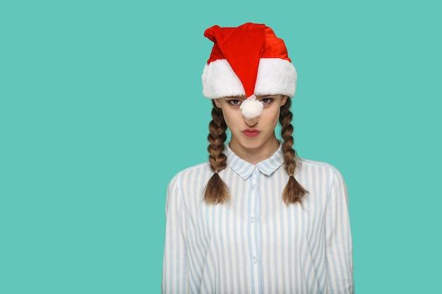 Conceito de ano novo. linda garota engraçada camisa listrada de azul claro no boné vermelho de natal e cabelo trançado em pé e olhando para a câmera e beijando. indoor, studio shot isolado sobre fundo verde.