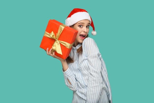 Conceito de ano novo. perguntou-se uma linda garota com uma camisa listrada azul claro e boné de natal em pé, segurando uma caixa de presente vermelha e olhando para a câmera com cara de espanto. interior isolado sobre fundo verde.