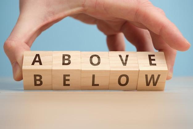 Conceito de antônimo acima e abaixo em blocos de madeira.