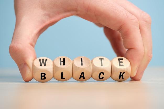 Conceito de antônimo de branco e preto em blocos de madeira.