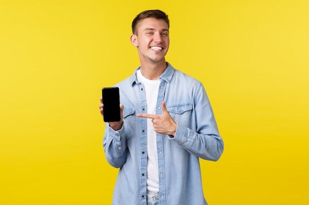Conceito de anúncio de lazer, tecnologia e aplicativo. cara loira sorridente feliz orgulhosa recomendando o aplicativo de smartphone, apontando o dedo para o celular para se gabar com suas fotos, fundo amarelo.
