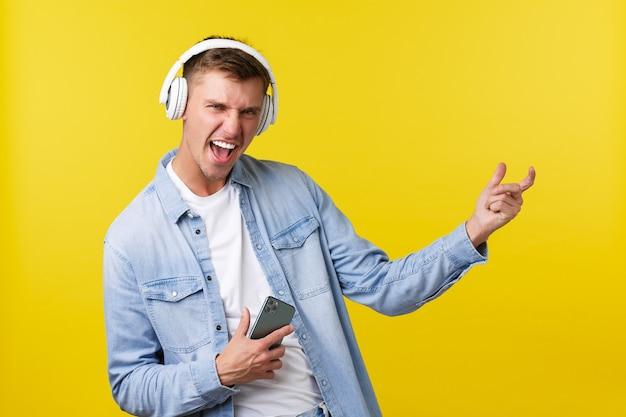 Conceito de anúncio de lazer, tecnologia e aplicativo. homem loiro feliz animado, curtindo música incrível, ouvindo músicas em fones de ouvido, segurando o telefone celular e tocando guitarra invisível.