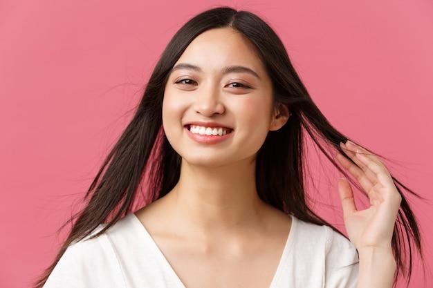Conceito de anúncio de produtos de salão de beleza, cuidados com os cabelos e cuidados com a pele. close-up de feliz linda mulher asiática satisfeita com o serviço de cabeleireiro, tocando o novo corte de cabelo e sorrindo satisfeito