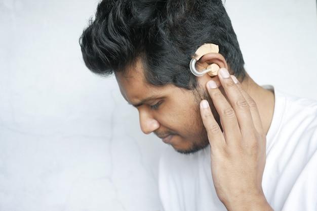 Conceito de aparelho auditivo, um jovem com problemas auditivos
