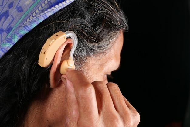 Conceito de aparelho auditivo, uma mulher idosa com problemas auditivos.