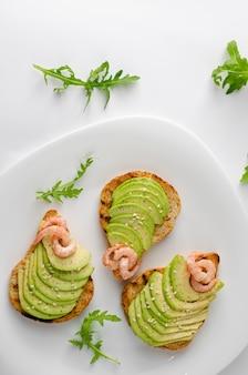 Conceito de aperitivo de dieta saudável. torradas de abacate com rúcula e camarão na chapa branca. tiro aéreo, vertical.