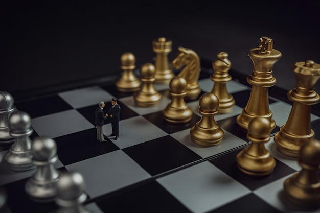 Conceito de aperto de mão de parceria de negócios em miniatura. aperto de mão de empresários bem sucedidos após bom negócio em xadrez de ouro e prata