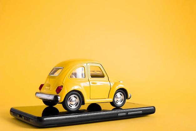 Conceito de aplicativo on-line móvel de táxi urbano. modelo de carro de táxi amarelo de brinquedo. mão segurando o telefone inteligente com aplicativo de serviço de táxi em exposição.